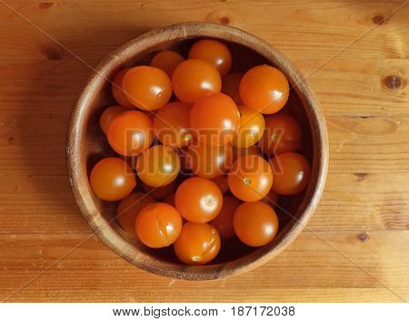 Orange cherry tomatoes in the bowl and near it at the wooden table. Fresh organic products, pure eco food. Rural still life - new vegetables harvest. Natural ingredients, top view.