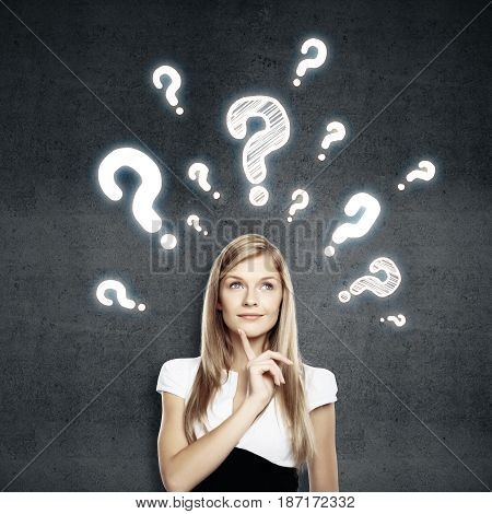Portrait of pretty european girl on dark concrete background with drawn question marks. Confusion concept