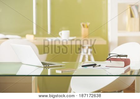 Glass desk with laptop and other items in modern office. Workplace concept