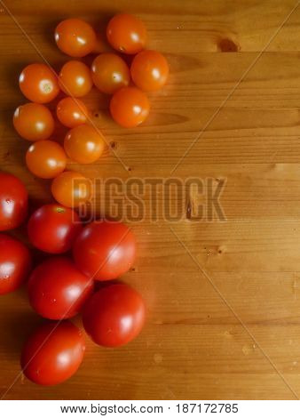 Vegetable background. Red ripe tomatoes and cherry at the wooden table. Fresh organic products, pure eco food. Rural still life - top view. With place for text.