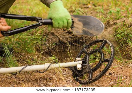 A metal detector for soil scanning a compact small shovel is very convenient for trips to nature a person digs a pit