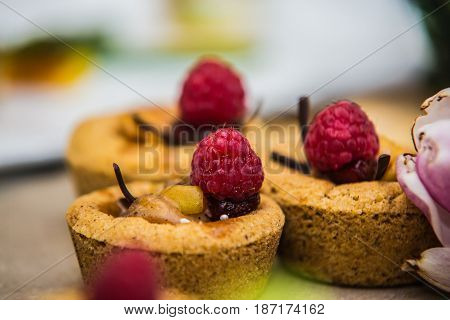 cupcakes decorated with fresh cream and raspberries.