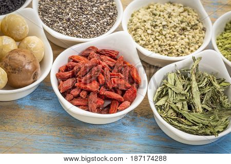 collection of superfoods in small ceramic bowls against rustic wood: macadamia nuts, hemp seed hearts, goji berry, stevia herb and chia seeds