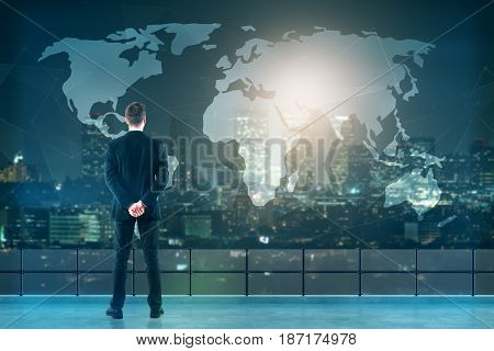 Back view of young businessman on rooftop looking at abstract map. Night city background. Travel concept