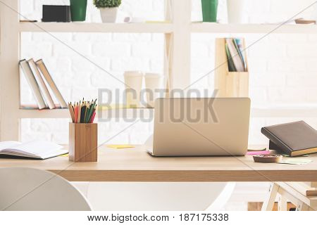 Horizontal image of open notebook placed on office desktop with supplies and other items
