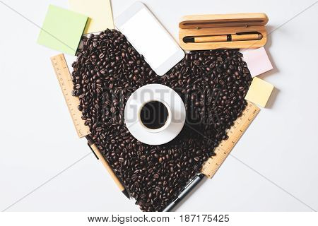 Top view of coffee cup beans shaped as a heart supplies and blank white smartphone. Morning concept
