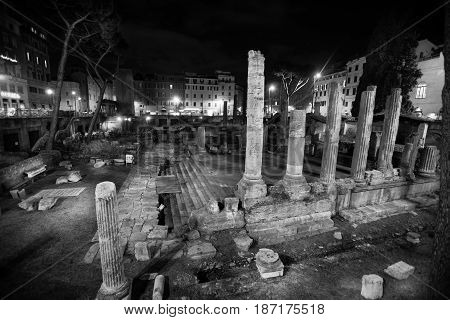Republican Roman temples, and the remains of Pompeys Theatre in Rome, Italy. Ancient Campus Martius. Night. Black and white.