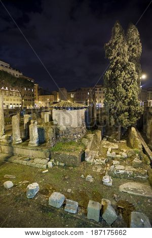 Republican Roman temples, and the remains of Pompeys Theatre in Rome, Italy. Ancient Campus Martius. Night.
