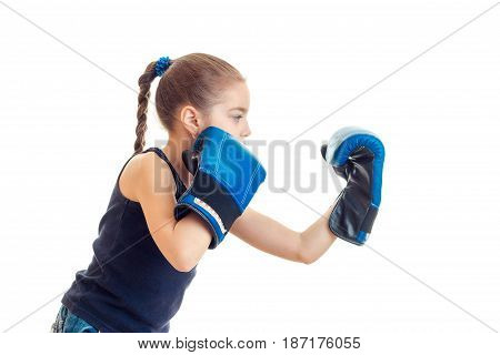 little girl with pigtail stands sideways and make large gloves isolated on white background