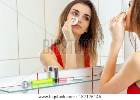 a young attractive girl looks in the mirror and rubs your face with a cotton disk close-up