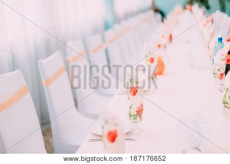 Decorative White Mantles And Colored Ribbons On Chairs At Festive Table. Chairs And Table Covered With Cloth.