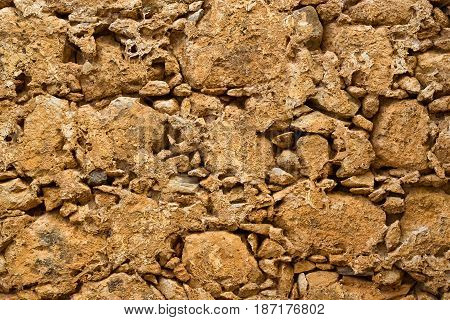 Texture stone-clay wall in Fortezza Castle Rethymno - fortress built by Venetians on hill Paleokastro. Crete Greece