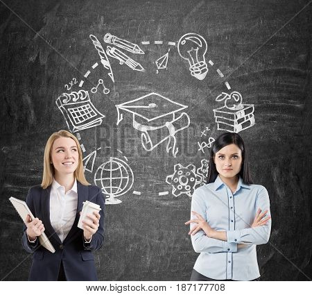 Enthusiastic blond woman with coffee and a clipboard is standing next to a serious determined competitor near a blackboard with education drawings