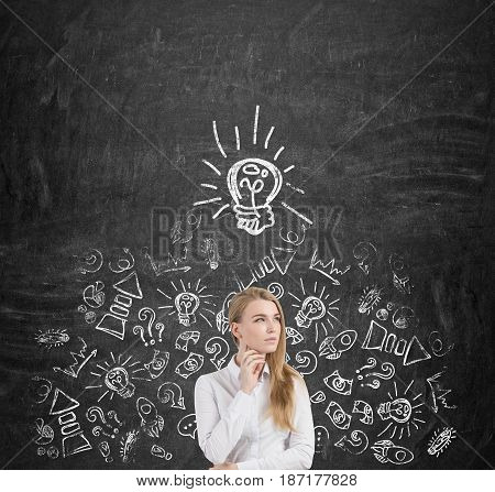 Portrait of a blond businesswoman standing near a blackboard and thinking about business growth. There is a light bulb above her head and many business icons