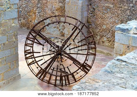 Remains of old rusty clock mechanism in basement in Fortezza Castle fortress with Bastion defense system on hill Paleokastro resort Rethymno. Greek architecture historical attractions. Crete Greece