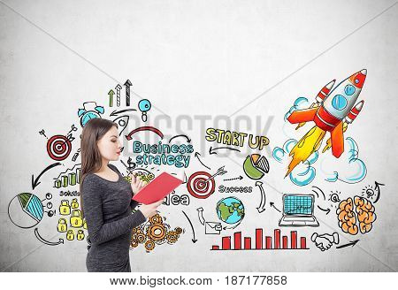 Side view of a young woman in a gray dress reading a red book near a concrete wall with a start up rocket sketch