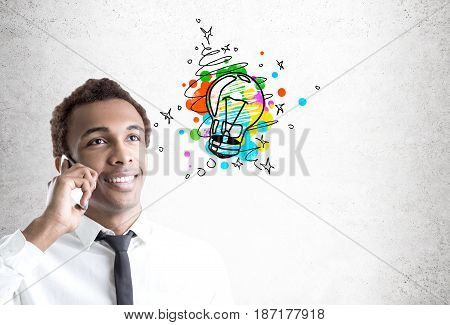 Portrait of a cheerful African American businessman smiling and talking on his smartphone near a concrete wall with a small light bulb sketch