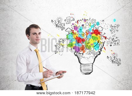 Portrait of a calm young businessman writing down his business ideas in a clipboard near a concrete wall with a large light bulb with icons