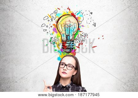 Portrait of a nerdy girl in glasses standing near a concrete wall and pointing at a colorful light bulb drawn on it above her head.