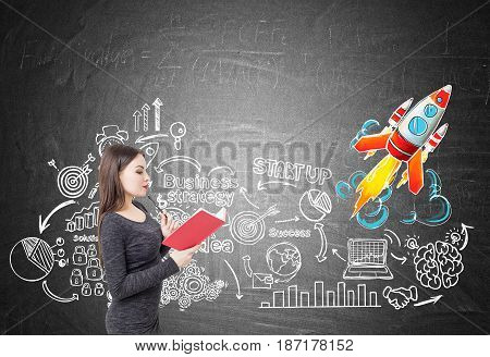 Side view of a young woman in a gray dress reading a red book near a blackboard with a start up rocket sketch