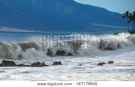 Tropical ocean waves breaking onto beach shoreline. Natures power and beauty displayed at scenic travel destination location, Maui, Hawaii.