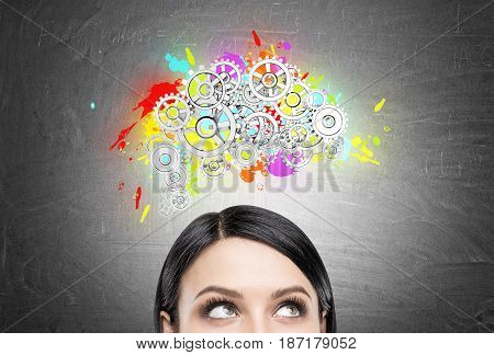 Close up of a head of a black haired woman standing near a chalkboard with a colored brain shape and gears on top of it.