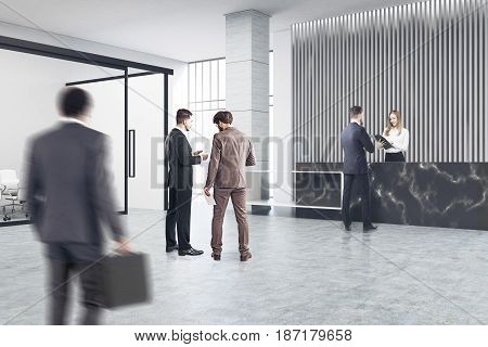 People near a black marble reception counter of original construction standing in an office lobby with a glass wall meeting room. 3d rendering