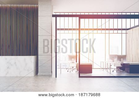 Marble reception counter is standing in a hall with a wooden wall next to a glass wall open office. 3d rendering toned image
