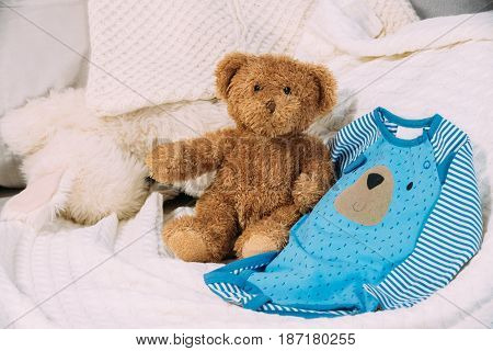 Funny Soft Toy Teddy Bear Near Child's Baby Clothes Rompers.