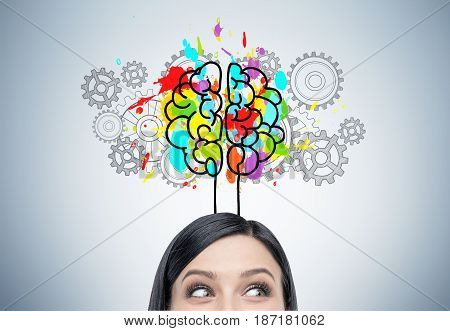 Close up of a woman s head with black hair. She is standing near a gray wall with a colorful brain sketch surrounded with gears.