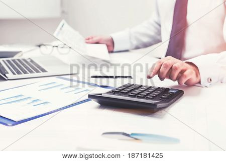 Close up of a businessman s hands using calculator standing on his desk. Concept of accounting. Toned image