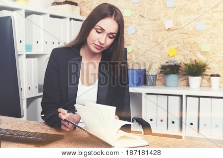Portrait of a serious businesswoman with long hair sitting at her table with a planner and making a schedule. Toned image