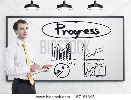 Portrait of a young businessman with a clipboard and a pencil standing near a whiteboard with four graphs and a word progress on it