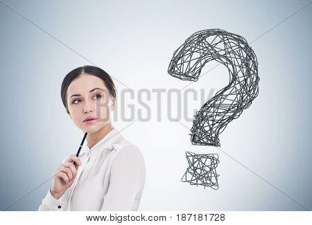Close up of a young businesswoman holding a pen. She is standing near a gray wall with a large question mark to the right of her