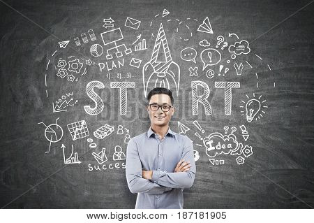 Portrait of a happy Asian businessman in glasses standing with crossed arm near a blackboard with a start up sketch