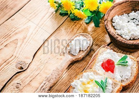Toasts with ricotta or farmers cheese, marmalade and honey. Raw wood background with wooden tableware and dandelions. Selective focus