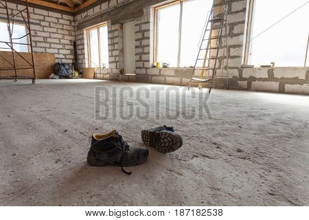 Interior of apartment during under renovation remodeling and construction (a pair of working shoes on the cement floor)