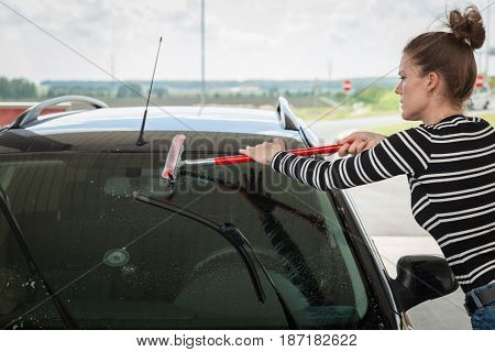 Young Woman Washing The Glass Of A Car At A Petrol Station