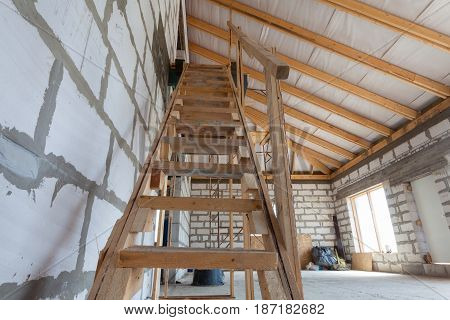 Interior of apartment during under renovation remodeling and construction (wooden stairs to the second floor)