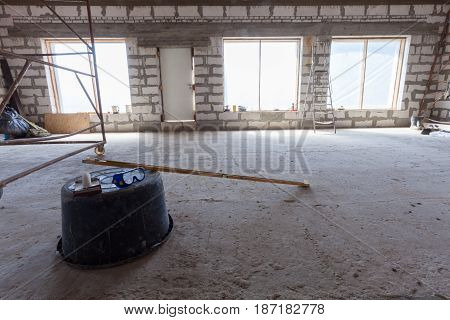 Interior of apartment with ladder during under renovation remodeling and construction (Plastic basin with protect glasses and level)