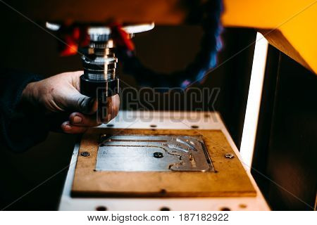 Close-up view of worker's hand which is changing cutter drill tool in CNC milling machine during treatment of raw steel piece fixed in moving table and already partly manufactured with several slots