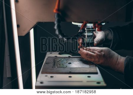 View of worker hands while he is changing drilling tool in CNC milling machine during pause of it cutting piece of aluminum in dark settings with LED backlight from lamps
