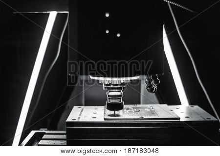 Futuristic black and white view of working CNC milling machine with moving table and static cutter tool rotating with high speed two LED lamps in background aluminum dust and chips around