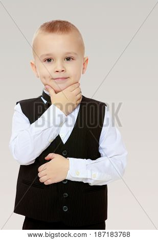 Beautiful little blond boy in a fashionable black suit with a tie.Boy what a thought.On a gray background.