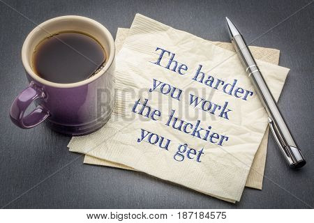 The harder you work, the luckier  you get - inspirational handwriting on a napkin with cup of coffee against gray slate stone background
