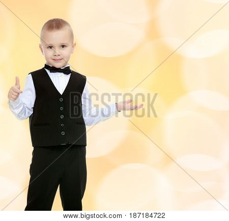 Beautiful little blond boy in a fashionable black suit with a tie.He shows his hand to the side.Brown festive, Christmas background with white snowflakes, circles.