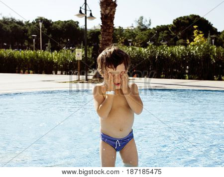 little cute real boy in swimming pool close up smiling, vacations in Turkey