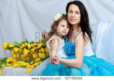 Beautiful young mother and little daughter in the same blue dresses on the sofa with a bouquet of flowers.