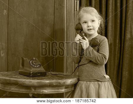 The little girl in the interior of the fifties of the last century holds the ear-piece of vintage phone. The girl calls her grandmother. Black-and-white photo. Retro style.