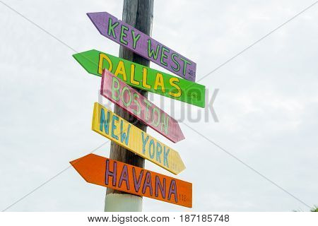 Colorful rustic direction signs on pole to major cities at Little Torch Key Maimi